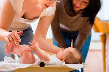 Hebamme mit Mutter wiegt Säugling