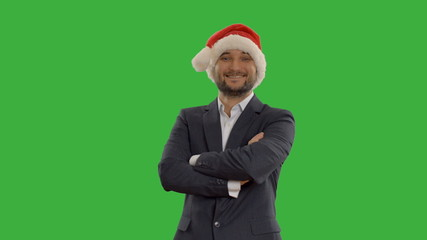 young businessman in hat of Santa Claus on green background
