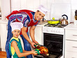 Family with child cooking chicken at kitchen.