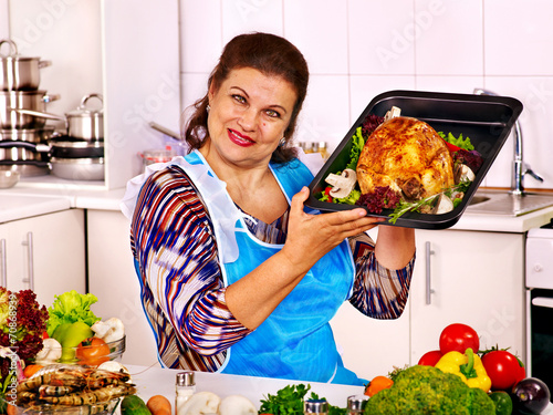 canvas print picture Mature woman preparing chicken at kitchen.