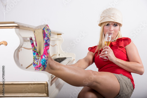 canvas print picture Frau mit High Heels Pumps und Safari Hut am Klavier