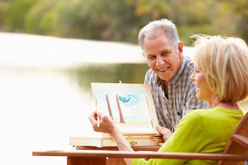 Senior Couple Sitting At Outdoor Table Painting Landscape