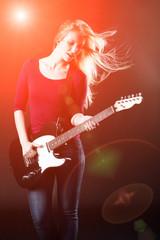 Blonde Frau spielt E-Gitarre