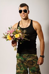 Young soldier in black undershirt holds bouquet of flowers