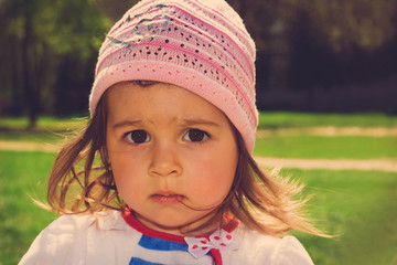 toned  portrait of Cute kid thinking at the park