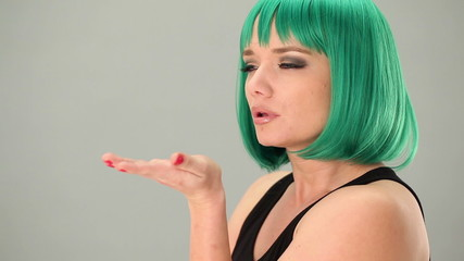 Sexy woman in a green wig blowing a kiss