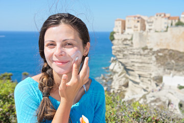 Young tourist girl spreads sunscreen on her face