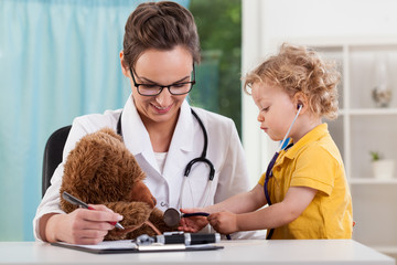 Cute kid diagnosing teddy bear