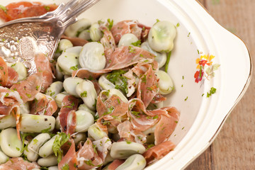close up broad beans and parma ham salads