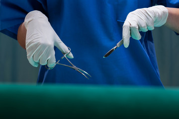 Surgeon's hands holding medical equipment