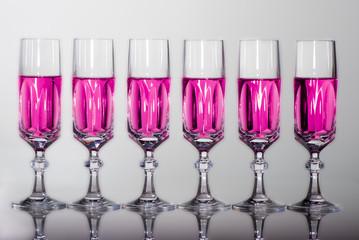 bicchieri cristallo in fila frontale con riflessi liquido rosa