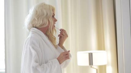 Seductive woman applying makeup
