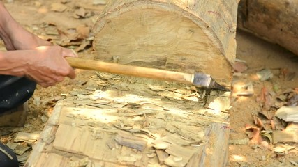 Carpenter cutting wood with axe.