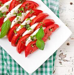 Caprese Salad. Tomato and Mozzarella slices with basil leaves.