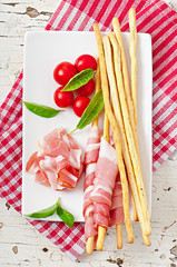Grissini bread sticks with ham, tomato and basil