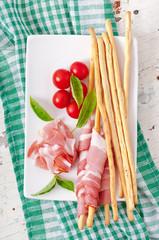 Grissini bread sticks with ham, tomato and basil