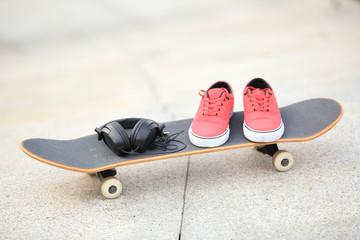 skateboard and sneakers at skatepark