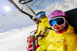 Skiing, ski lift, ski resort - happy skiers on ski lift