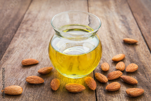 Leinwandbild Motiv Almond oil in glass bottle and almonds
