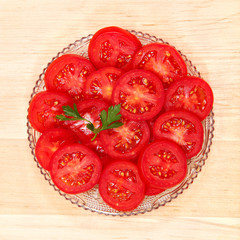 Fresh vegetable tomato slices in a glass dish.