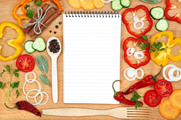 Vegetables, spices and notepad for recipes, on table.