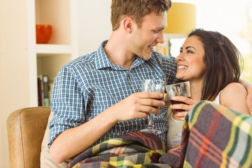 Happy young couple relaxing on the couch with red wine