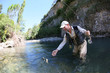 canvas print picture - Fly fisherman catching a fario trout in river
