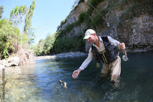 canvas print picture Fly fisherman catching a fario trout in river