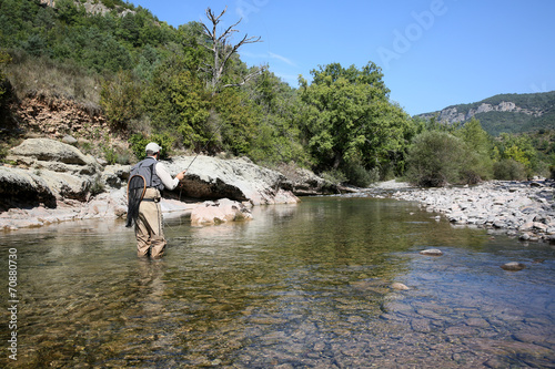 Foto op Canvas Vissen Fly fisherman flyfishing in river