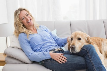 Smiling blonde woman petting her golden retriever