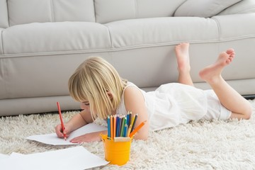 Smiling litlle girl drawing lying on the floor