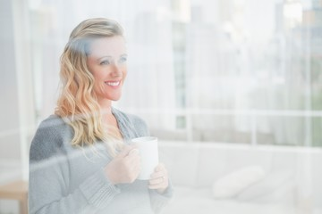 Smiling blonde woman holding mug of coffee looking away