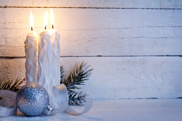 Christmas candles on vintage white boards background