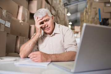 Worried warehouse manager with laptop