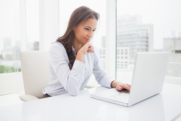 Happy businesswoman using laptop at her desk