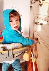 Baby boy pulling drawers in the kitchen