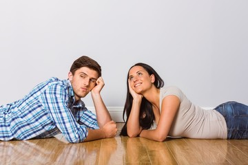 Young couple lying on floor smiling