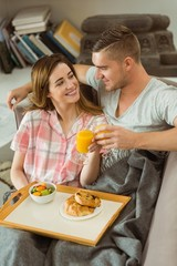 Cute couple relaxing on couch with breakfast