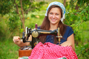 Smiling woman with retro hand sewing machine