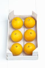 Weisse Holzkiste mit frischen Orangen