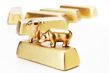 Goldener Bulle und Bär Figuren auf Goldbarren