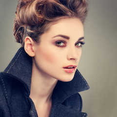 elegant young woman in a grey overcoat on a grey