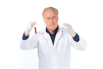 Man lab technician looks at test tubes.