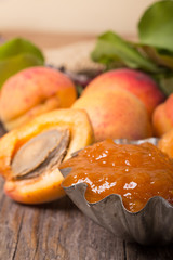 Handmade apricot jam with fresh fruits on wooden table