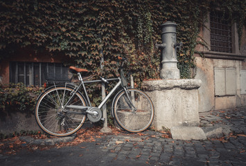 Bicycle parked near drinking tap on the street in Rome, Italy