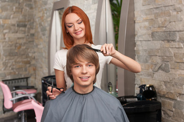Female hairdresser cutting hair of man client