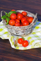 Tomatoes with basil in basket outdoors