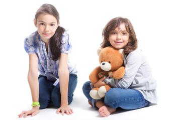 bambine sedute a terra con teddy bear