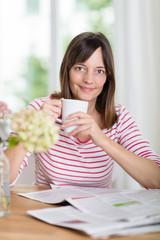 lächelnde frau mit kaffee und zeitung