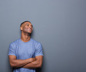 Happy african man laughing with arms crossed